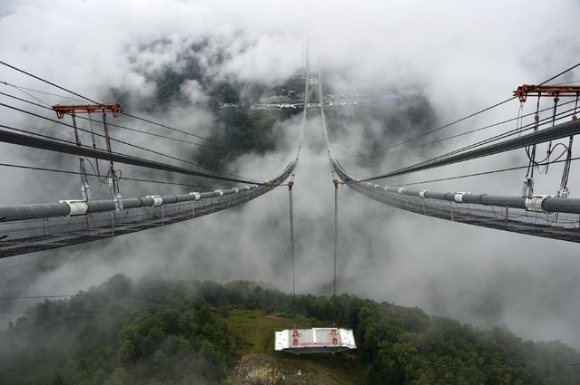 The installation of the first steel box girder onto a large-span suspension bridge over Longjiang River is seen in Baoshan, Yunnan province, July 30, 2015. The 2,470 metre long bridge will become the biggest suspension bridge in Asia's mountainous area when the three-year-long project finishes by June 2016, with an estimated cost 1,465,000,000 yuan ($236,011,500). (Photo by Reuters/Stringer)