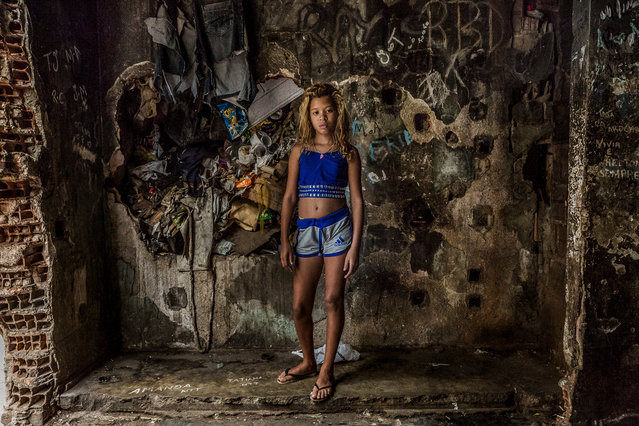 Roberta, 11, stands in front of one of the old elevator shafts, which are now filled with rubbish. (Photo by Tariq Zaidi/The Guardian)