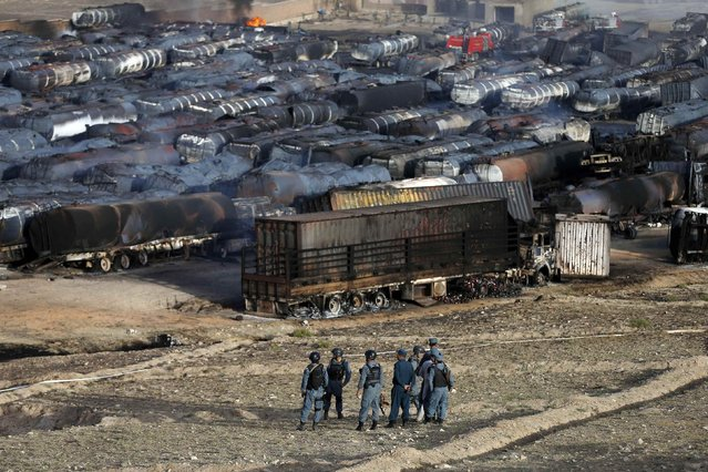 Afghan policemen stand at the site of burning fuel trucks after an overnight attack by the Taliban on the outskirts of Kabul July 5, 2014. Taliban insurgents set fire on Saturday to about 200 oil tanker trucks supplying fuel for NATO forces in an attack just outside the Afghan capital Kabul, police said. (Photo by Mohammad Ismail/Reuters)