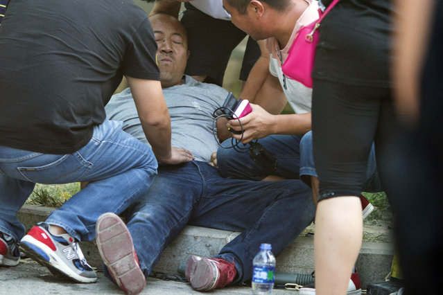 A man crying about the death of his son collapses outside a hospital receiving victims of explosions in northeastern China's Tianjin municipality, Thursday, August 13, 2015. (Photo by Ng Han Guan/AP Photo)