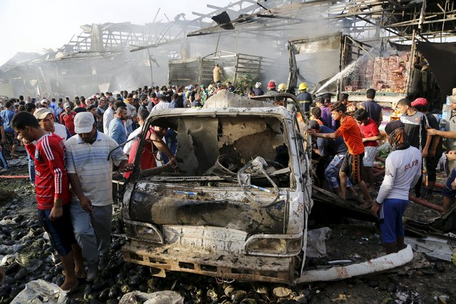 Residents gather at the site of a truck bomb attack at a crowded market in Baghdad August 13, 2015. (Photo by Wissm Al- Okili/Reuters)