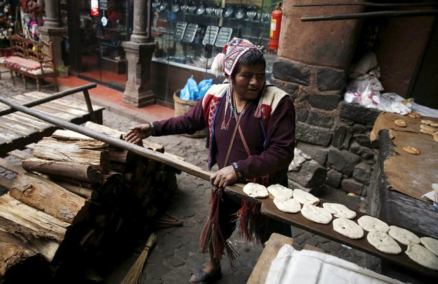 Baker Eulogio Pillco bakes traditional bread using an oven made of clay in the town of Pisac, Cusco, August 13, 2015. (Photo by Pilar Olivares/Reuters)