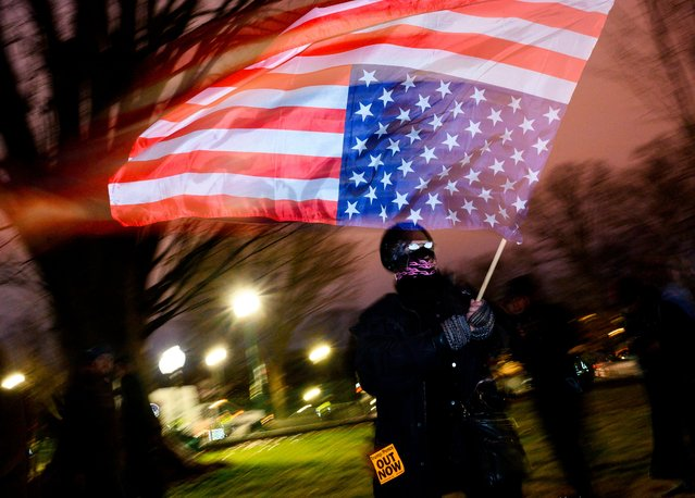 A protester waves a US national flag upside down, in a sign of distress, outside the Capitol in Washington, DC, on February 5, 2020, after the US Senate acquited the US president in his impeachment trial. The US Senate acquitted President Donald Trump of abuse of power and obstruction of Congress following a historic two-week trial. (Photo by Andrew Andrew Caballero-Reynolds/AFP Photo)