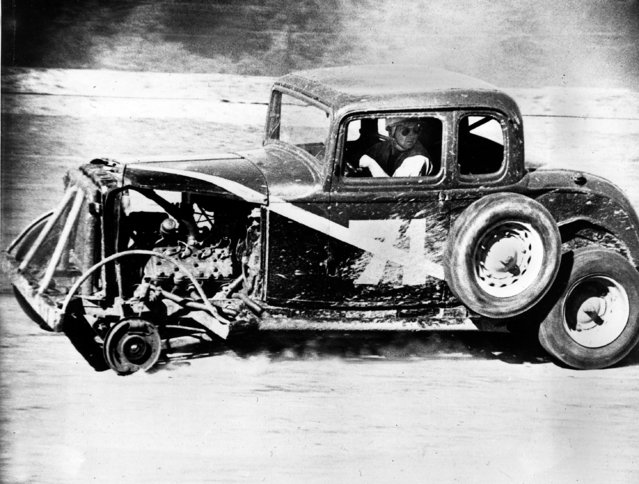 Walter Ragan, of Conowingo, Md., turns and watches his left front wheel fly by his stock car on the Mason-Dixon Raceway at Oxford, Pa., Saturday, June 14, 1952. The wheel separated from the brake drum as the car continued to move and Ragan pulled into the pits without difficulty. (Photo by AP Photo)