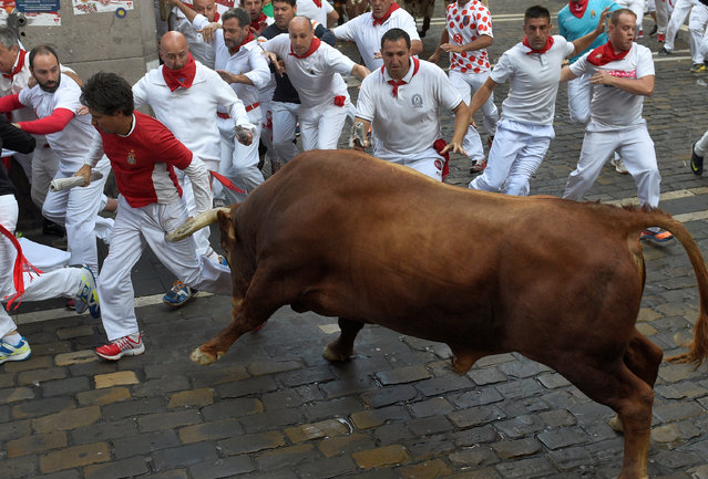 A Cebada Gago fighting bull charges runners at the Estafeta corner during the second running of the bulls at the San Fermin festival in Pamplona, northern Spain July 8, 2016. (Photo by Eloy Alonso/Reuters)