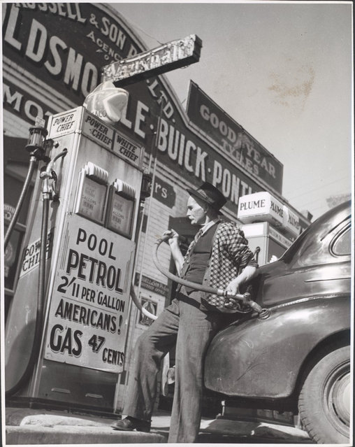William Russell putting the four gallon monthly ration of petrol into a customer's car, Drouin, Victoria, ca. 1944. Home town Australia. Drouin's biggest service station (there are two) is owned by a company consisting of 80 year old William D. Russell and his family. Mr Russell is putting the four gallon monthly ration of gas onto a customers car