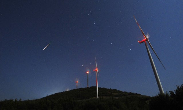 A meteor streaks across the sky during the Perseid meteor shower at a windmill farm near Bogdanci, south of Skopje, in the early morning August 13, 2014. The annual Perseid meteor shower reaches its peak on August 12 and 13 in Europe, although the lunar glare of a nearly full moon (Supermoon) makes it difficult to view the meteor shower this year, according to NASA. (Photo by Ognen Teofilovski/Reuters)