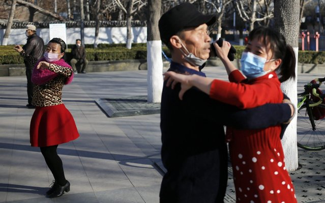 People wearing masks dance at a park in Beijing, China, 13 March 2020. The World Health organization (WHO) officially declared the coronavir​us outbreak a pandemic on 11 March 2020. (Photo by Wu Hong/EPA/EFE)