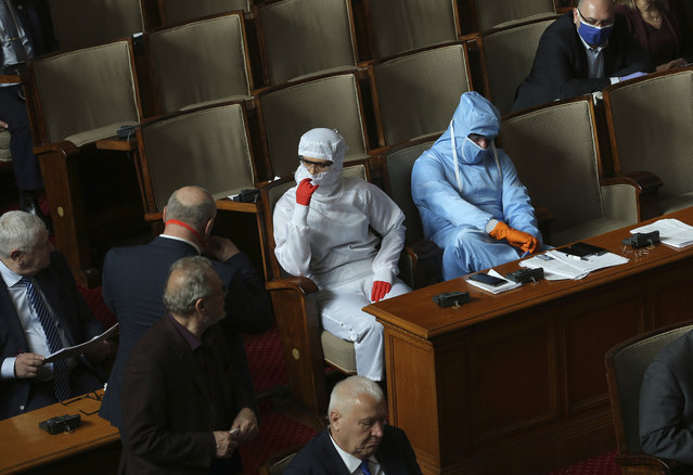 Vesselin Mareshki, right, leader of Bulgarian Political party Volya, and an MP from from his party wear protective suits during Parliamentary session in the Bulgarian National Assembly in Sofia, Bulgaria, on Friday March 20, 2020. (Photo by Vesselin Borishev/AP Photo)