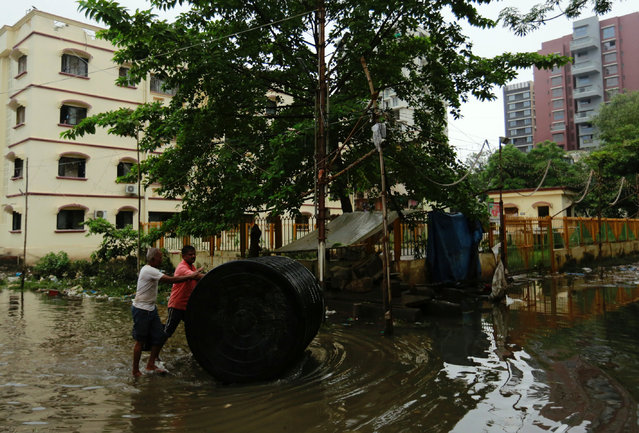 Men push a water tank through a partially flooded street at a residential area in Mumbai, August 30, 2017. (Photo by Danish Siddiqui/Reuters)