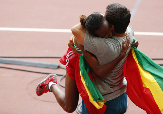 Mare Dibaba of Ethiopia is hugged after winning the women's marathon at the 15th IAAF Championships at the National Stadium in Beijing, China August 30, 2015. (Photo by David Gray/Reuters)