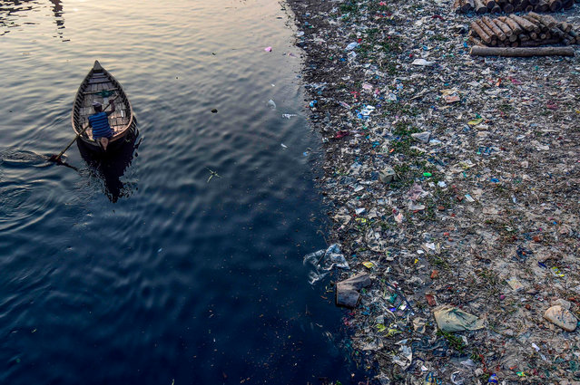 A man paddles on a boat as plastic bags float on the water surface of the Buriganga river in Dhaka on January 21, 2020. Bangladesh's high court has ordered the shutdown of 231 factories that have contributed to Dhaka's main river becoming one of the world's most polluted, a lawyer said on January 21. (Photo by Munir Uz Zaman/AFP Photo)