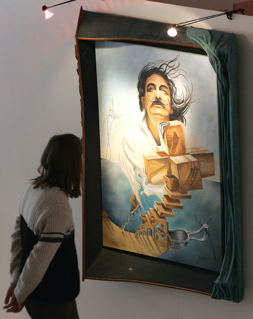"""A visitor watches for a painting of Salvador Dali at the Salvador Dali exhibition """"Die Ausstellung"""" on March 19, 2008 in Berlin, Germany. The spanish painter Salavdor Dali was a skilled draftsman, best known for the striking and bizarre images in his surrealist work. His painterly skills are often attributed to the influence of Renaissance masters. His best known work, The Persistence of Memory, was completed in 1931. (Photo by Andreas Rentz)"""