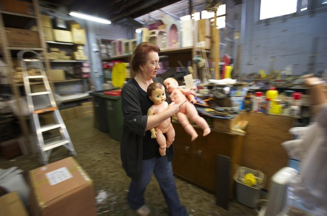 Australian doll repairer Kerry Stuart, a 25-year veteran at Sydney's Doll Hospital, carries spare dolls to be used for parts in repairing customer's dolls, July 15, 2014. (Photo by Jason Reed/Reuters)