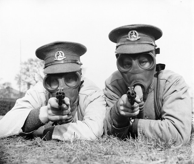 Soldiers of the Royal Norfolk Regiment at Aldershot, Hampshire getting used to revolver shooting while wearing a gas mask. UK, 28th March 1936.  (Photo by Reg Speller/Fox Photos)