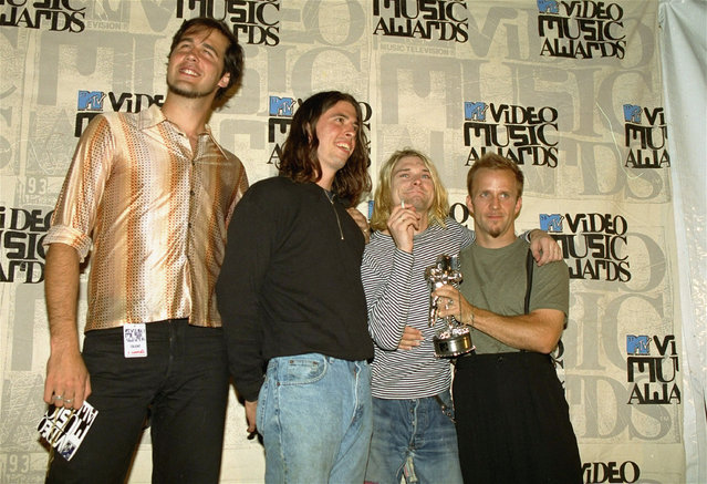 """Grunge rockers Nirvana pose after receiving an award for best alternative video for  """"In Bloom"""" at the 10th annual MTV Video Music Awards Thursday, September 2, 1993 in Universal City, California. Members from left are, Chris Novoselic, Dave Grohl, and Kurt Cobain.  Man at right is not a member of the band and is unidentified. (Photo by Mark J. Terrill/AP Photo)"""