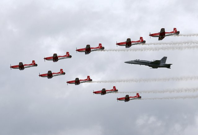 Swiss Air Force PC-7 Team performs with a F/A 18 Hornet aircraft during the Air14 airshow at the airport in Payerne August 31, 2014. The Swiss Air Force celebrates their 100th anniversary with the biggest airshow in Europe this year. (Photo by Denis Balibouse/Reuters)