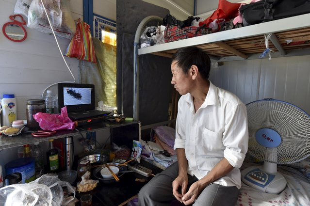 A migrant worker watches a live broadcast of a military parade marking the 70th anniversary of the end of World War Two, at his dormitory in Hefei, Anhui province, China, September 3, 2015. (Photo by Reuters/Stringer)