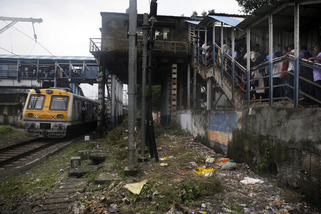 A local train drives past a pedestrian bridge where a stampede occurred earlier in the morning in Mumbai, India, Friday, September 29, 2017. The stampede broke out on a crowded pedestrian bridge connecting two railway stations in Mumbai during the Friday morning rush, killing a number of people police said. (Photo by Rafiq Maqbool/AP Photo)