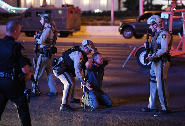 Police officers stop a man who drove down Tropicana Ave. near Las Vegas Boulevard and Tropicana Ave, which had been closed after a mass shooting at a country music festival that left at least 2 people dead nearby on October 2, 2017 in Las Vegas, Nevada. The man was released. (Photo by Ethan Miller/Getty Images)
