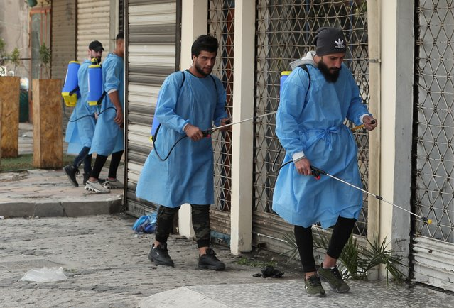 Iraqi volunteers spray disinfectant as a precaution against the coronavirus during a curfew, in a market in Baghdad, Iraq, Sunday, March 22, 2020. (Photo by Hadi Mizban/AP Photo)