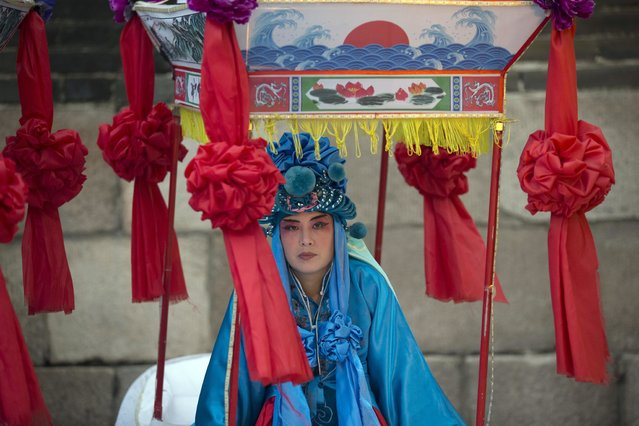 A performer prepares to take part in a ceremony to mark the one year anniversary of Beijing's successful bid for the 2022 Winter Olympics and Paralympics at the Badaling Great Wall in Beijing, Sunday, July 31, 2016. Come 2022, Beijing will be the first city to have hosted both the Summer and Winter Olympic Games. (Photo by Ng Han Guan/AP Photo)