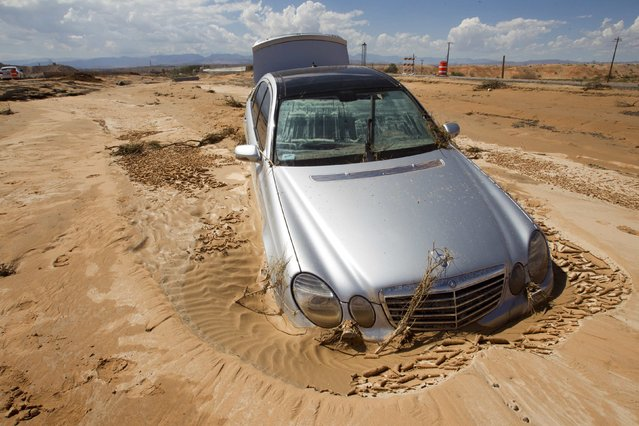 A Mercedes sedan is pictured partially submerged in mud in the median of Interstate 15 near Glendale, Nevada September 9, 2014. About 1 mile (1.6 km) of freeway was severely damaged by the runoff from Monday's storm. The Nevada Department of Transportation expects to have two lanes open by the weekend, a spokesman said. (Photo by Steve Marcus/Reuters/Las Vegas Sun)