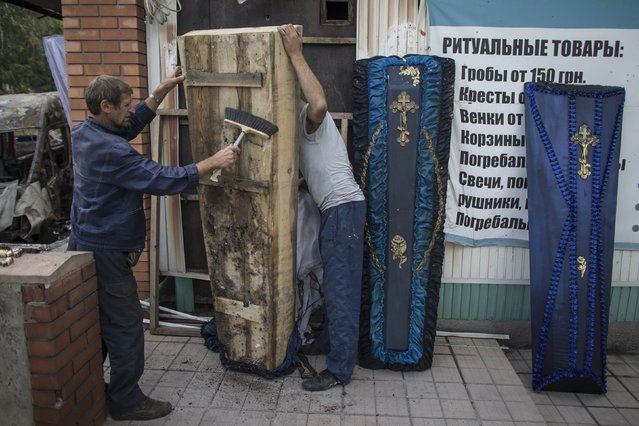 "People clean a coffin from an undertaker's showroom that was recently shelled in Donetsk, eastern Ukraine, September 16, 2014. Ukraine's parliament passed a law on Tuesday that will give ""special status"" to the separatist-minded eastern regions including a degree of self-governance for a three-year period, parliamentary deputies, who attended the closed session, said. (Photo by Marko Djurica/Reuters)"