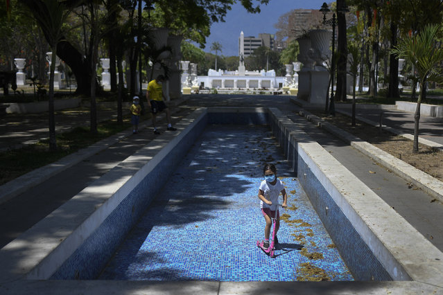 A child wearing a face mask rides her scooter inside an empty water fountain at Los Proceres boulevard in Caracas, Venezuela, Sunday, April 26, 2020. Venezuela's government allowed for children to go outside and play for eight hours, after it had imposed quarantine to help stop the spread of the new coronavirus. (Photo by Matias Delacroix/AP Photo)