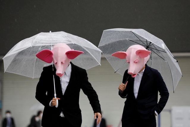 Youtubers wearing masks of pigs film a video at a shopping district which has fewer people than usually amid the coronavirus disease (COVID-19) outbreak in Tokyo, Japan, May 19, 2020. (Photo by Kim Kyung-Hoon/Reuters)
