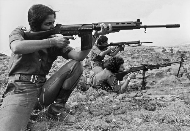 Young Christian Lebanese women, who are members of Kataeb Phalangist party, show their skill in handling arms while they train in a village between Christian-controlled eastern port of Jounieh and the Christian village of Zahle in the west Lebanon on September 9, 1976. The Lebanese civil war erupted in April 1975. (Photo by Erich Stering/AFP Photo)