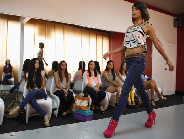 A girl walks down the runway during a class at a modelling academy in Caracas, Venezuela, on September 20, 2014. Venezuela's famed models and aspiring beauty queens are struggling to doll themselves up. In a country that glorifies voluptuous women and opulent beauty pageants, even basics like deodorant are now at times tricky to find as strict currency controls have led to a scarcity of dollars for imported goods. (Photo by Carlos Garcia Rawlins/Reuters)