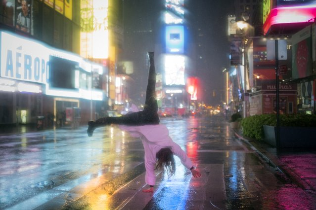 A visitor in a bathrobe does a cartwheel in the rain while visiting Times Square in New York October 29, 2012.  As Hurricane Sandy aimed straight for them, promising to hammer the place they live with lashing winds and extensive flooding, New Yorkers seemed to be all about nonchalance on Monday morning – an attitude that didn't last into the afternoon. (Photo by Adrees Latif/Reuters)
