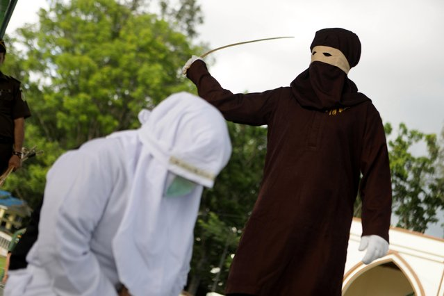 A sharia executor, know as algojo, during a public caning punishment in Jantho, Aceh Besar Regency, Indonesia, 17 November 2017. Ten people were sentenced to public caning for adultery in Aceh, the only province in Indonesia which implements sharia law. (Photo by Hotli Simanjuntak/EPA/EFE)