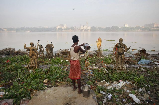 A man pours water on the polluted banks of river Ganges beside the idols of Hindu god and goddess that were immersed during the Durga Puja festival in Kolkata October 20, 2010. (Photo by Reinhard Krause/Reuters)