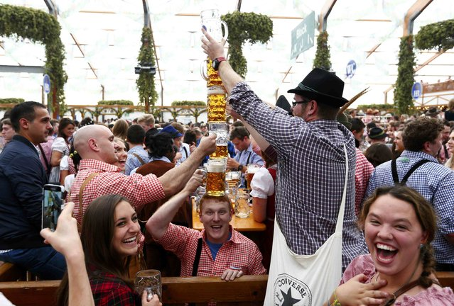 Visitors joke with beer mugs on the first day of the 182nd Oktoberfest in Munich, Germany, September 19, 2015. (Photo by Michaela Rehle/Reuters)