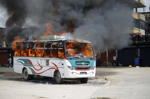 A passenger bus set on fire by unidentified protesters is pictured during the nationwide strike, called by the opposition parties against the proposed constitution, in Kathmandu, Nepal September 20, 2015. (Photo by Navesh Chitrakar/Reuters)