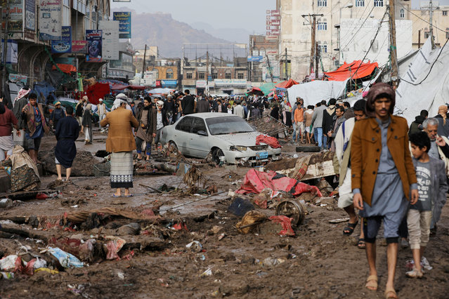 People walk on a damaged street at an area flooded by heavy rains in Sanaa, Yemen on April 14, 2020. (Photo by Khaled Abdullah/Reuters)