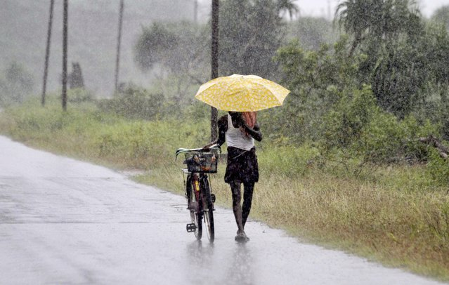 An Indian man holds an umbrella to protect himself from the heavy rains near Gopalpur, in Ganjam district, 140 kilometers (87 miles) south of Bhubaneswar, India, Saturday, October 11, 2014. (Photo by Biswaranjan Rout/AP Photo)