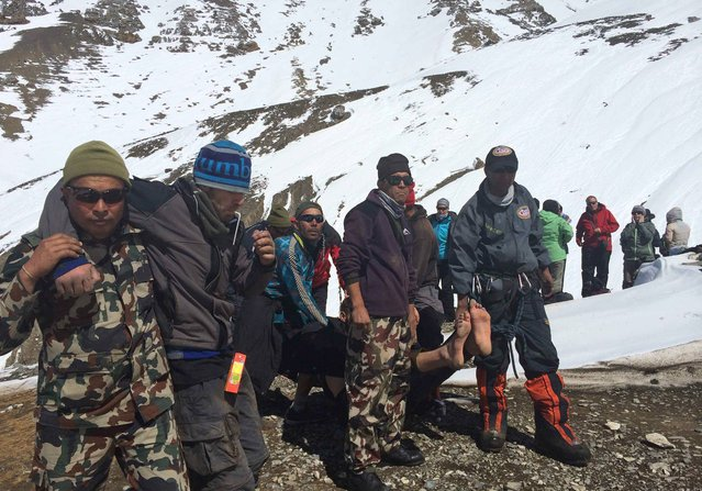 In this handout photo provided by the Nepalese army, rescue team members carry avalanche victims to safety at Thorong La pass area in Nepal, Friday, October 17, 2014. Rescuers widened their search Friday for trekkers stranded since a series of blizzards and avalanches battered the Himalayas in northern Nepal early this week, leaving at least 29 foreigners and locals dead, officials said. (Photo by AP Photo/Nepalese Army)