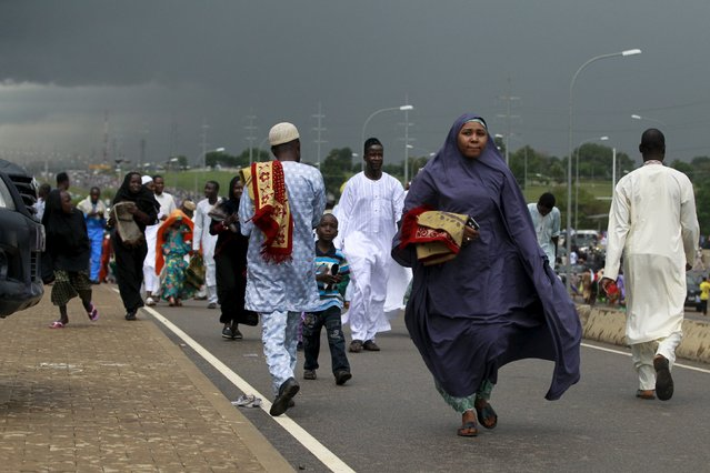 People are seen returning from the prayer grounds after Sallah prayers during Eid al-Adha in Abuja, Nigeria, September 24, 2015. (Photo by Afolabi Sotunde/Reuters)