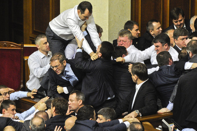 Lawmakers fight around the rostrum during the first session of Ukraine's newly elected parliament in Kiev, Ukraine, December 13, 2012. (Photo by Sergei Chuzavkov/Associated Press)
