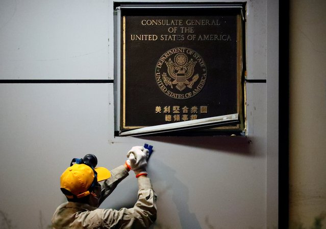 A man works to remove the U.S. Consulate plaque at the U.S. Consulate General in Chengdu, Sichuan province, China, July 26, 2020. (Photo by Thomas Peter/Reuters)