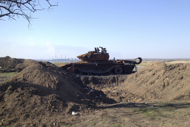 A destroyed T-72 tank, which presumably came from Russia, is seen on a battlefield near a trench outside separatist-controlled Starobesheve in eastern Ukraine October 2, 2014. (Photo by Maria Tsvetkova/Reuters)