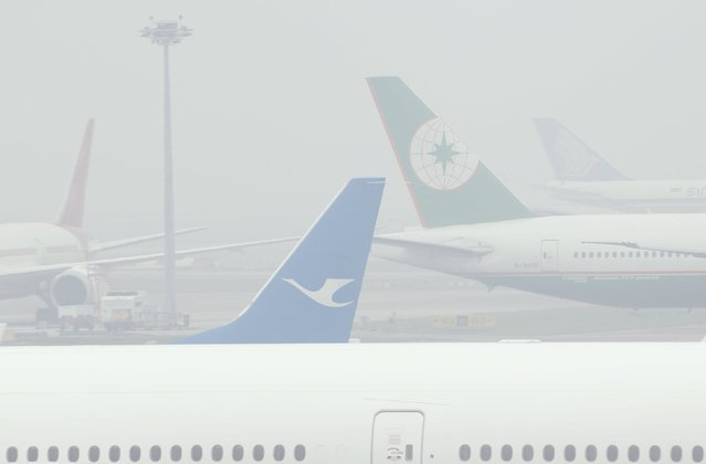 Planes sit on the tarmac in Singapore's Changi Airport September 29, 2015. The 3-hour haze Pollutant Standards Index (PSI) reached a high of 245 at 1300 SGT (0500 GMT) on Tuesday, according to the National Environment Agency. (Photo by Edgar Su/Reuters)