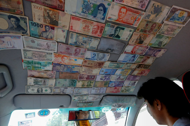 A taxi driver has the roof of his vehicle decorated with bank notes from around the world while working in Bangkok,Thailand July 20, 2016. (Photo by Jorge Silva/Reuters)