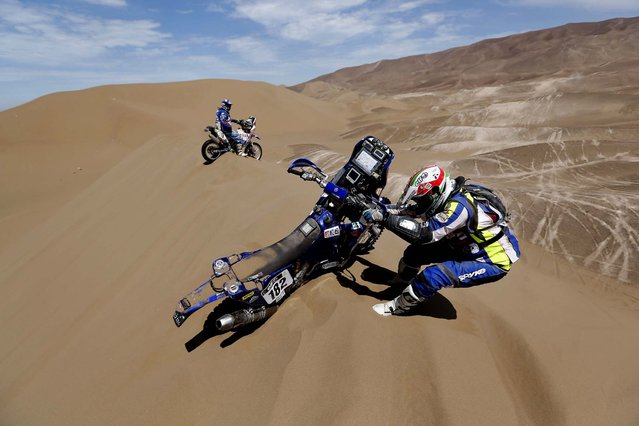 Yamaha Paolo Sabbatucci of Italy, right, tries to get his motorcycle out of the sand as Yamaha teammate rider John Mckendrick of Chile waits for him during the 6th stage. (Photo by Victor R. Caivano/Associated Press)