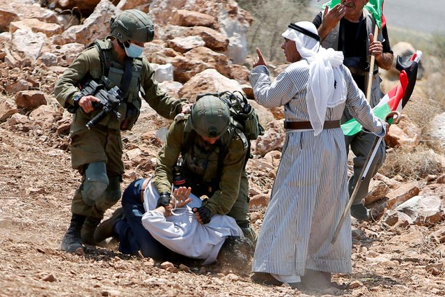 Israeli soldiers detain a Palestinian demonstrator during a protest against Jewish settlements near Tulkarm in the Israeli-occupied West Bank on August 20, 2020. (Photo by Raneen Sawafta/Reuters)