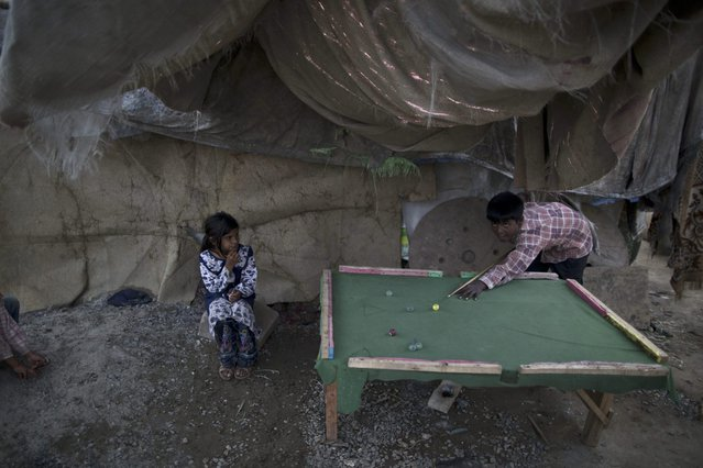 Pakistani Christian boy, Suhail Pervez, 9, plays snooker on a table he built, in a slum that hosts Christian families, in Islamabad, Pakistan, Thursday, March 27, 2014. (Photo by Muhammed Muheisen/AP Photo)