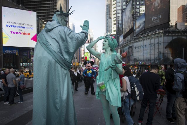 A woman (R) who gave her name as Allyson, and who is dressed up as the Statue of Liberty high fives as she teases and harasses a man who is also dressed up as a Statue of Liberty while she films a comedy segment in Times Square in the Manhattan borough of New York October 8, 2015. The woman was following the man who poses for tips with tourists around and joking with him. (Photo by Carlo Allegri/Reuters)
